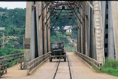 Share the road, share the bridge. An old truck crosses an old rail road bridge in northern Vietnam Royalty Free Stock Image