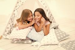 Share secrets concept. Girls cute children lay relaxing in teepee bedroom. Cute space for leisure. Modern interior. Includes comfortable teepee houses. Secret royalty free stock photos