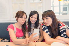 Share something in mobile phone. Asian lady in the restaurant and share something in mobile phone with her friends royalty free stock images