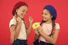Share sweet donut. Girls in beret hats hold glazed donut red background. Kids playful girls ready eat donut. Friendship. And generosity. Sweets shop and bakery royalty free stock photo