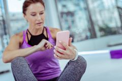 Musing mature woman posting photo from training. Share your life. Selective focus of modern smartphone carried by female hand which typing message royalty free stock images