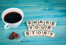 Share your story. Coffee mug and wooden letters on wooden background Royalty Free Stock Images