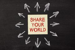Share Your World. Sticky note pasted on a blackboard background with a lot chalk arrows stock photos