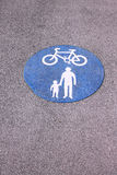 Shared foot and cycle path roundel sign painted on path. Shared cycle and pedestrian path blue roundel sign painted on path surface Stock Photos