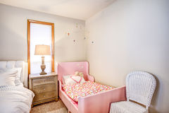 Shared master bedroom interior with girl`s pink bed Royalty Free Stock Image