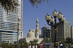 Shariah. Glimpse of Shariah, UAE, with mosque dominated by skyscrapers and street lamp in the foreground Stock Photo