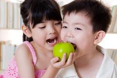 Sharing. Asian kids sharing an apple Stock Photos