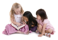 Sharing a book. Three young girls sharing a book. Diversity in friends Royalty Free Stock Photos