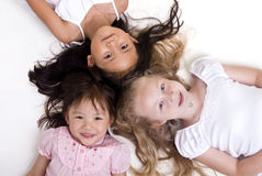 Sharing a book. Three young girls sharing a book. Diversity in friends Royalty Free Stock Photo