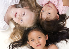 Sharing a book. Three young girls sharing a book. Diversity in friends Royalty Free Stock Image