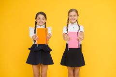Sharing book love. Happy little girls holding books with colorful covers on yellow background. Cute small children. Smiling with encyclopedia or hand books royalty free stock images