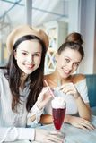 Sharing cocktail. Two pretty girls sharing yummy cocktail while enjoying time in cafe on weekend or between classes in college Royalty Free Stock Photo