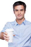 Sharing coffee with you. Handsome young man in blue shirt holding a coffee cup outstretched and smiling while standing isolated on white Stock Images