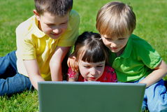 Sharing a computer. Three youngsters share the use of a laptop computer outdoors in an open field Royalty Free Stock Photos