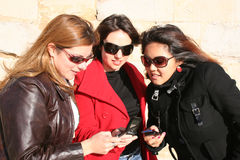 Sharing data. Three young women looking at their mobile phones Stock Image