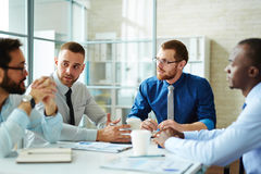 Sharing and discussing ideas. Male employees listening to colleague at briefing royalty free stock image