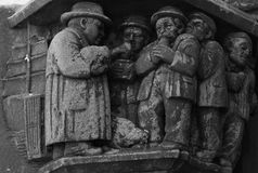 Sharing the food. Shot in black and white. Placed on the facade of this historic building, sculpture on the capital representing a group of male figures sharing Stock Image