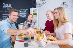 Sharing fries at the table Royalty Free Stock Photography