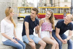 Sharing funny stories. Shot of four students sitting on a wall and telling each other stories Stock Image