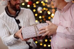 Sharing gift on Christmas-Father giving present to son. Close up Stock Photo