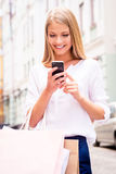 Sharing good news with friend. Close-up of beautiful young smiling woman holding shopping bags and mobile phone while standing outdoors Royalty Free Stock Photo