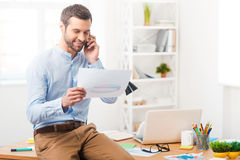 Sharing good news. Handsome young man in shirt talking on the telephone and some document while sitting on desk in office Royalty Free Stock Image