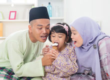 Sharing ice cream. Eating ice cream. Muslim family sharing an ice cream. Beautiful Southeast Asian family living lifestyle at home Stock Photos