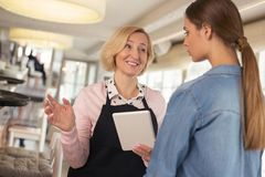Delighted waitress discussing menu with her employer. Sharing ideas. Inspired blond waitress holding a tablet and talking with her young employer Stock Images