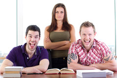 Sharing a joke. Two male students share a joke, the women doesn't approve Royalty Free Stock Images