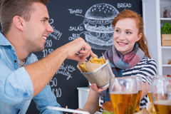 Sharing junk food. Smiled girl is sharing junk food with her friend Royalty Free Stock Image