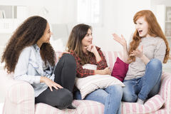 Sharing latest news with her best friends. Three young women sitting on a sofa and chatting Stock Images