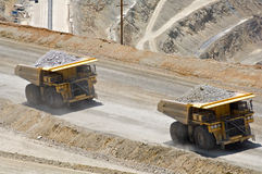 Sharing the load. Two monster dump trucks carry 250 ton loads of rock out of an open pit mine royalty free stock photo