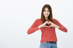 Sharing love and friendliness with friends. Attractive positive female student in casual outfit, showing heart gesture. Over chest and smiling broadly stock photos