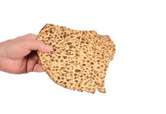 Sharing Matzoh. A hand reaching out to share a piece of round matzoh Stock Images