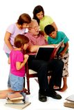 Sharing Memories. Senior man viewing old scrapbooks with four of his grandchildren royalty free stock images