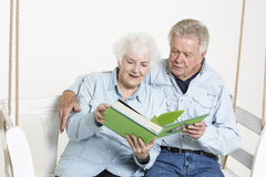 Sharing memories. Senior couple is looking through pictures in an album Royalty Free Stock Photography