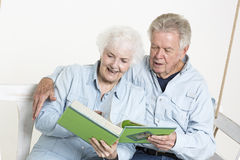 Sharing memories. Senior couple is looking through pictures in an album Royalty Free Stock Photos