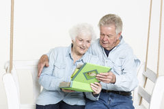 Sharing memories. Senior couple is looking through pictures in an album Royalty Free Stock Images