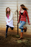 Sharing the moment. Two pretty young best friend country girls, both with long brown hair standing by a barn door smiling at each other sharing their time Stock Photos