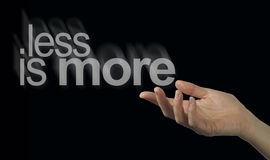 Sharing a less is more philosophy. Female hand appearing to release a phrase LESS IS MORE on a black background Royalty Free Stock Photos