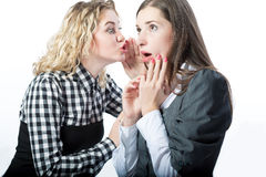 Sharing news with each other. Two young surprised girlfriends sharing news with each other isolated over white background royalty free stock photos