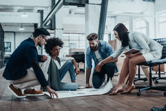 Sharing opinions. Group of confident business people discussing something while looking at blueprint laying on the floor Royalty Free Stock Photography