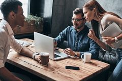 Sharing opinions. Group of young confident business people discu. Ssing something while spending time in the office Royalty Free Stock Image