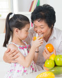 Sharing orange juice. Asian family drinking orange juice. Happy Asian grandchild sharing cup of fresh squeeze fruit juice with grandmother at home Royalty Free Stock Photography
