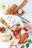 Sharing platter meat ham cheese olives wine. Charcuterie concept. Overhead view of cured meats, cheese with olives, on rustic table stock photography