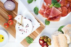 Sharing platter meat ham cheese olives wine. Charcuterie concept. Overhead view of cured meats, cheese with olives, on rustic table royalty free stock image