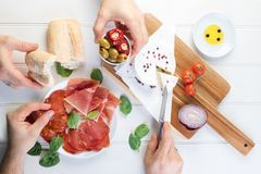 Sharing platter meat ham cheese olives wine. Charcuterie concept. Overhead view of cured meats, cheese with olives, on rustic table royalty free stock photo