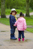 Sharing A Puddle. A little boy and girl wearing wellington boots, holding hands and sharing a puddle in a park royalty free stock photography