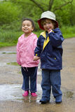 Sharing A Puddle. A little boy and girl wearing wellington boots holding hands and sharing a puddle in a park Stock Image