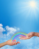 Sharing a Rainbow moment with you. Female hand and male hand facing up with a transparent rainbow connecting them together on a blue sky, fluffy clouds and Royalty Free Stock Photos